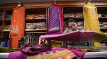 Balwinder Kaur, owner of Chandni Fashion, folds clothing while working her mobile phone. Chandni Chowk plaza at the corner of Ray Lawson Boulevard and McLaughlin Road is a popular destination for people looking for Indian groceries, goods and services. (Fred Lum/The Globe and Mail)