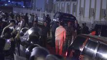 Egyptian police officers guard a convoy carrying former president Hosni Mubarak's sons Alaa and Gamal outside Sharm el-Sheikh courthouse. (Amr Nabil/Amr Nabil/AP)