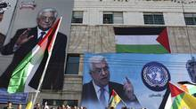 "Banners depicting Palestinian President Mahmoud Abbas cover a wall during a rally in the West Bank city of Hebron, supporting the resolution that would change the Palestinian Authority's United Nations observer status from ""entity"" to ""non-member state"" Nov. 29, 2012. (AMMAR AWAD/REUTERS)"