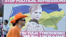 FILE - In this June 8, 2012 file picture Dutch soccer fans pass a protest poster that calls for release of former Ukrainian Prime Minister Yulia Tymoshenko in Kiev, Ukraine. (Nigel Treblin/AP)