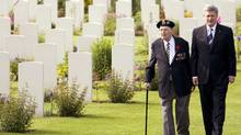 Prime Minister Stephen Harper walks with Phil LeBreton, 88, a Normandy campaign veteran from Montreal of the Queen's Own Rifles of Canada, at the Canadian military cemetery in Beny-sur-Mer on Saturday. (CHRIS HELGREN)
