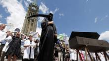 A protester wearing a Grim Reaper costume stands on Parliament Hill during a rally on July 10, 2012 in Ottawa to protest the federal government's cuts to science policies. The government's 2013 budget has reopened debates in the scientific community. (Fred Chartrand/The Canadian Press)