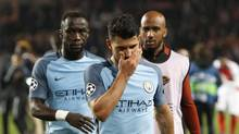Manchester City's Sergio Aguero, centre, leaves the pitch after being eliminated in the Champions League quarter-finals. (Claude Paris/AP)