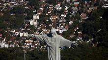 The Christ the Redeemer statue stands on top of Corcovado Mountain in this aerial photograph of Rio de Janeiro, Brazil, on July 4, 2013. (Dado Galdieri/Bloomberg)