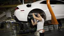 An employee works on a Cadillac model at the General Motors Oshawa assembly plant in this file photo. (Moe Doiron/The Globe and Mail)