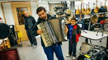 Natanael Dobra and his son Joshua try an accordion at the Joe Chithalen Memorial Musical Instrument Lending Library in Kingston. (Johnny C Y Lam)
