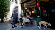 Boyd Thomson, left, owner of The Wilder Snail, chats with regular customer Keith Jardine as Thomson's dog Fern walks outside his coffee shop in the Strathcona neighbourhood. (DARRYL DYCK for the globe and mail)