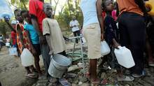 Earthquake survivors in Port-au-Prince wait in line to collect water this week. Aid groups in Canaday say they've been warned by the Conservatives not to weigh in on policy. (Mario Tama/Mario Tama/AFP/Getty Images)