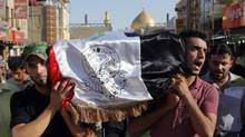 Mourners carry the flag-draped coffin of Abdullah Swadi, a member of an Iraqi volunteer forces group who was killed during clashes with Islamic militants, his family said, during his funeral procession in the Shia holy city of Najaf on July 8, 2014. (JABER AL-HELO/ASSOCIATED PRESS)