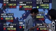 Pedestrians holding mobile phones walk past a stock quotation board displaying various countries' share indices, outside a brokerage in Tokyo September 9, 2013. (YUYA SHINO/REUTERS)