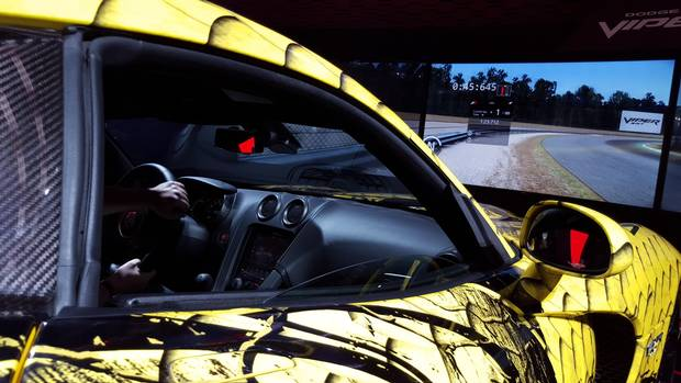 "It's the ultimate race simulator. Brave souls climb inside a full-size Dodge Viper – which shakes, bounces and swerves on the spot – as video ""racers"" try to overtake the competition on the screen ahead. (Darren McGee/The Globe and Mail)"