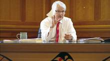 "Outgoing B.C. Premier Gordon Campbell sits behind the ""Leadership Desk"" at his office in Victoria. The hand-crafted red cedar desk, created in the form of a bentwood box and adorned with First Nation's iconography, was designed by internationally-known B.C. artist Arthur Vickers. (John Lehmann/The Globe and Mail/John Lehmann/The Globe and Mail)"
