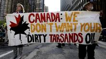 FILE PHOTO: Demonstrators hold a sign as they protest against the Keystone Pipeline and the Alberta Tar Sands outside of the Canadian Consulate in downtown Chicago, Thursday, May 17, 2012. (Nam Y. Huh/AP)