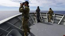 Gunner Richard Brown (L) of Transit Security Element looks through binoculars as he stands on lookout with other crew members aboard the Australian Navy ship HMAS Perth as they continue to search for missing Malaysian Airlines flight MH370 in this picture released by the Australian Defence Force April 10, 2014. (HANDOUT/REUTERS)