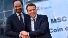 This file photo taken on Feb. 1, 2016, shows Emmanuel Macron shaking hands with mayor of Le Havres Edouard Philippe in Saint-Nazaire, western France. (LOIC VENANCE/AFP/Getty Images)