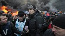 Opposition leader and former WBC heavyweight boxing champion Vitali Klitschko, middle, addresses protesters near the burning barricades between police and protesters in central Kiev, Ukraine, Thursday Jan. 23, 2014. Klitschko dove behind the wall of black smoke engulfing much of downtown Kiev on Thursday, pleading with both police and protesters to uphold the peace until the ultimatum, demanding that Yanukovych dismiss the government, call early elections and scrap harsh anti-protest legislation that triggered the violence. (Sergei Chuzavkov/AP)
