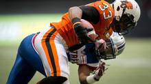 B.C. Lions' Andrew Harris breaks a tackle by Montreal Alouettes' Jerald Brown, back, and scores a touchdown during second half CFL action in Vancouver, B.C., on Saturday July 19, 2014. (DARRYL DYCK/THE CANADIAN PRESS)