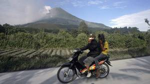 Villagers ride a motorcycle while covering their mouths at the district of Tanah Karo outside the city of Medan, North Sumatra, as the Mount Sinabung volcano spews smoke in the background on August 28, 2010.