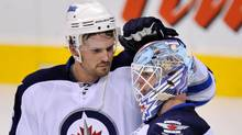 Winnipeg Jets defenceman Ron Hainsey (L) celebrates with goalie Chris Mason after they defeated the Carolina Hurricanes during NHL pre-season action in Winnipeg, September 28, 2011. (Fred Greenslade/Reuters)