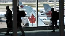 Passengers walk past Air Canada planes on the runway at Pearson International Airport in Toronto. (MIKE CASSESE/REUTERS)