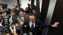 Tatsuo Kainaka, the head of the panel investigating Olympus Corp., is surrounded by reporters after a news conference in Tokyo on Dec. 6, 2011. An independent panel issued a damning report into the $1.7-billion accounting scandal at Japan's Olympus Corp, urging legal action against executives behind the cover-up and the replacement of others who knew about it. (KIM KYUNG-HOON/KIM KYUNG-HOON/REUTERS)