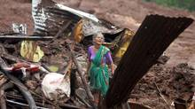 An elderly Indian woman cries as she searches for surviving family members in the debris of her home, destroyed by landslide in Malin village, in the western Indian state of Maharashtra, Wednesday, July 30, 2014. (Press Trust of India/AP)