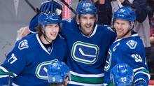 From left to right, Ben Hutton, Brandon Sutter and Henrik Sedin of the Vancouver Canucks celebrate Sutter's goal against the Chicago Blackhawks on Nov. 19, 2016. (Darryl Dyck/The Canadian Press)