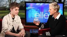 Ellen DeGeneres, right, listens to Canadian singer Justin Bieber as she holds a box containing strands of his hair during an appearance on The Ellen DeGeneres Show. The hair will be auctioned off and the proceeds donated to Gentle Barn. (Michael Rozman/AP)