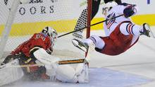 Columbus Blue Jackets' Cam Atkinson (R) goes flying through the air after he scored the game-winning goal on Calgary Flames goalie Miikka Kiprusoff in a shootout during their NHL game in Calgary, Alberta March 18, 2012. REUTERS/Todd Korol (Todd Korol/Reuters)