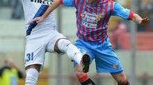 Inter Milan defender Alvaro Pereira jumps for the ball with Catania midfielder Mariano Izco (Carmelo Imbesi/AP)