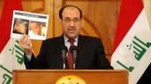 Iraqi's Prime Minister Nuri al-Maliki shows a picutre of al Qaeda's Iraq leader Abu Ayyub al-Masri after he was killed by Iraqi and U.S forces during a raid operation, in Baghdad April 19, 2010. (HO/REUTERS)