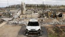 A charred vehicle and home in the Beacon Hill neighbourhood of Fort McMurray, Alberta. (CHRIS WATTIE/REUTERS)