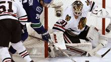 Chicago Blackhawks goalie Antti Niemi makes a third period save on Vancouver Canucks right wing Mikael Samuelsson as Blackhawks' Brian Campbell (51) checks during Game 3 of their NHL Western Conference semi-final hockey game in Vancouver, British Columbia May 5, 2010. (ANDY CLARK/REUTERS)
