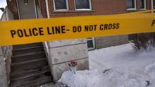 A bouquet of rose is surrounded by police tape at a Mississauga apartment Jan 2, 2013 where the body of a toddler was found. (Moe Doiron/The Globe and Mail)