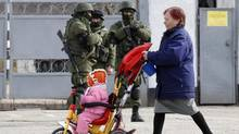 A woman pushes a child as uniformed men, believed to be Russian servicemen, stand guard in front of a Ukrainian serviceman, seen behind a fence, near a Ukrainian military base in the village of Perevalnoye, outside Simferopol, March 6, 2014. (VASILY FEDOSENKO/REUTERS)