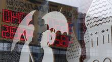 A board displaying currency exchange rates is reflected in a shop window in central Moscow, August 29, 2014. (SERGEI KARPUKHIN/REUTERS)