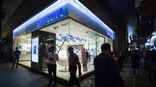 Pedestrians walk past a Samsung store at night in Hong Kong on Oct. 11. Samsung is discontinuing the Galaxy Note 7 after it, and its replacement, was found to be prone to overheating. (Justin Chin/Bloomberg News)