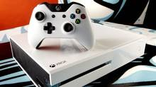 "Xbox One Special Edition ""Sunset Overdrive"" Bundle, featuring a sleek white console and wireless controller, a digital copy of the game, and special Day One edition in-game items. (Microsoft)"