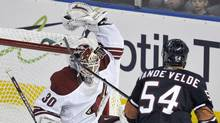 Phoenix Coyotes' goalie Ilya Bryzgalov (L) makes a glove save as Edmonton Oilers' Chris Vande Velde looks for a rebound during the second period of their NHL hockey game in Edmonton March 17, 2011. (DAN RIEDLHUBER)