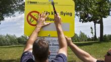 Municipal workers post signs prohibiting kite flying at Miliken Park, in Scarborough last summer. (Kevin Van Paassen/Kevin Van Paassen/The Globe and Mail)