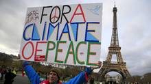 An activist hold a poster during a demonstration near the Eiffel Tower, in Paris, Saturday, Dec.12, 2015 during COP21. (Thibault Camus/AP)
