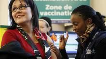Canada's Health Minister Leona Aglukkaq receives her H1N1 flu shot from Claire Bahati at a clinic in Ottawa November 27, 2009. (BLAIR GABLE)