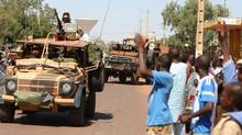 Residents of San in central Mali clap as French troops pass through on Friday. (Harouna Traore/AP)