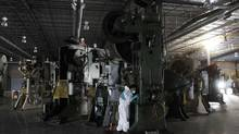 A worker maintains machinery at Meco Corp. in Saltillo, Mexico in this file photo. The economy grew 0.5 per cent in the July-September period. (TOMAS BRAVO/REUTERS)