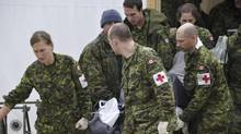 Members of the Canadian Armed Forces carry a victim of a plane crash in Resolute Bay, Nunavut, Saturday, Aug.20, 2011. (THE CANADIAN PRESS/HO-Department of National Defence-Sgt. Norm McLean/THE CANADIAN PRESS/HO-Department of National Defence-Sgt. Norm McLean)
