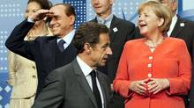 French President Nicolas Sarkozy walks past Italy's President Silvio Berlusconi and German Chancellor Angela Merkel as he takes his place for family photo at the G20 Summit in Toronto. (Adrian Wyld/Adrian Wyld/The Canadian Press)