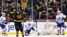 Toronto Maple Leafs' Jonathan Bernier (45) kneels beside the net as Boston Bruins' Patrice Bergeron, foreground, celebrates a goal by Brad Marchand during the third period of an NHL hockey game in Boston, Saturday, Jan. 16, 2016. The Bruins won 3-2. (Michael Dwyer/AP)
