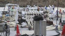 In this March 10, 2014, file photo, workers wearing protective gear work at the Fukushima Dai-ichi nuclear power plant in Okuma, northeastern Japan in their attempt to stop the leakage of radioactive water that has accumulated at the crippled nuclear power plant. (Koji Sasahara/AP)