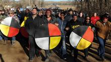 People hold ceremonial objects during a protest march against the Dakota Access pipeline near the Standing Rock Indian Reservation in Mandan, N.D., U.S., Nov. 12, 2016. (STEPHANIE KEITH/REUTERS)