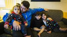 Bilal Alfaloji with his three kids at the Sandman Hotel in Vancouver, where a large number of Syrian refugee are temporarily housed. (John Lehmann/The Globe and Mail)